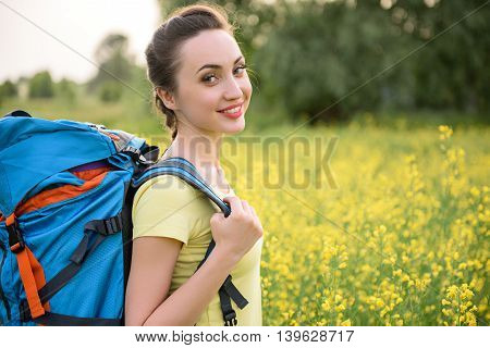 Happy young woman is making touristic trip. She is standing on flower meadow and carrying backpack. Lady is looking at camera and smiling