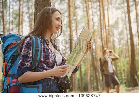 Young woman is reading a map and smiling. She is standing and carrying touristic backpack. Man is standing and looking into binoculars in forest