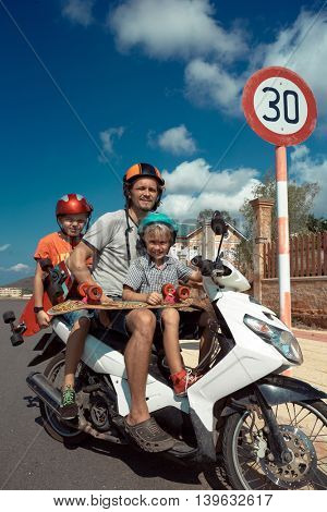 Family of father and two kids on motorbike.
