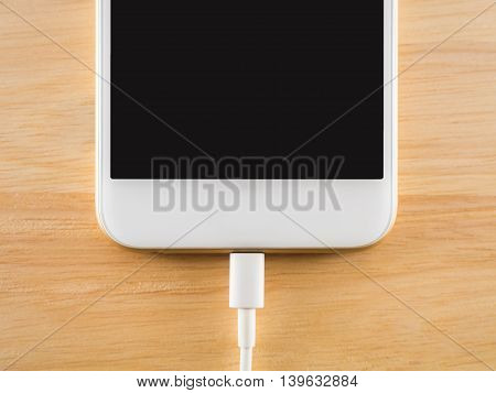Top view (Flat Lay) of smart phone charging with USB cable on wooden texture background