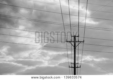 Black and white electricity pole with crossing wires in front of a cloudy sky
