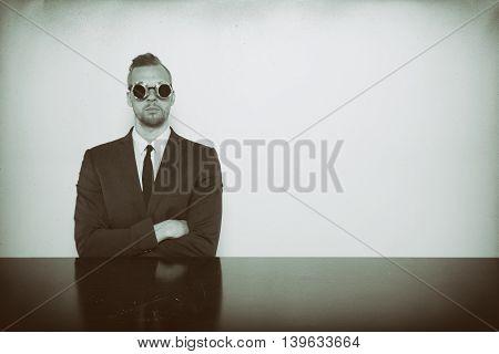 Businessman sitting at office desk hand crossed