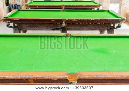 Three old green empty billiard tables in a row outside
