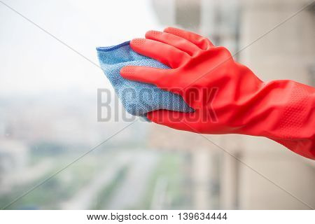 man cleaning the window with red glove