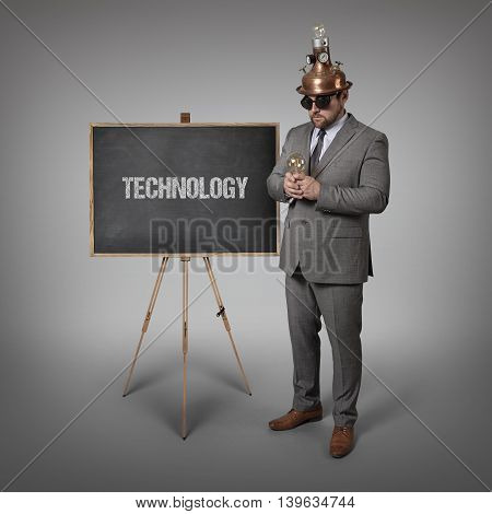 Technology text on blackboard with science businessman holding light bulb