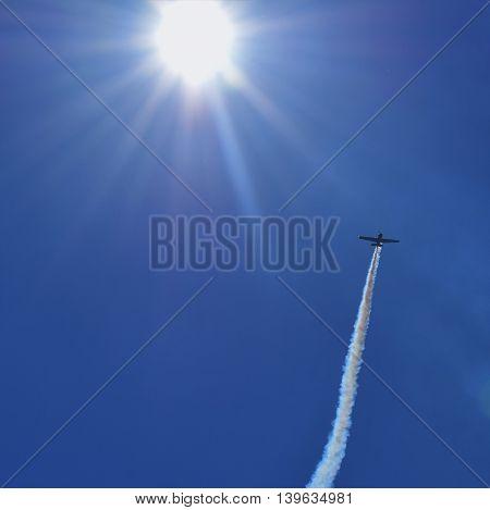 An airplane flies into the sun at an air show.