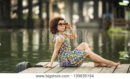 Young beautiful Asian woman sits on a wooden river pier.