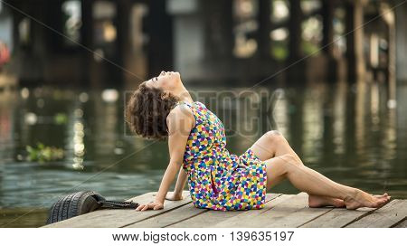 Young beautiful Asian woman posing on a wooden river pier.