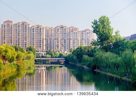 ShanghaiChina 07/22/2016 Residential high rise buildings in a park like area with a river and a bridge reflecting the scenery in Shanghai