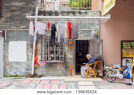 Qingdao China 04/10/2016 Old Chinese grandpa is sitting in front of his tiny poor house with clothes hanging out to dry reading a newspaper