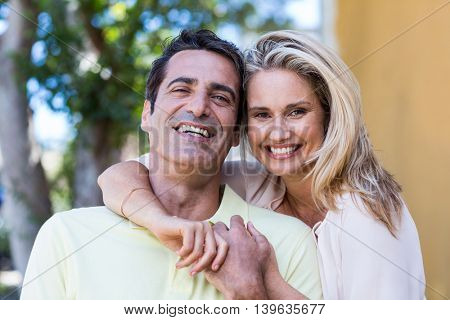 Portrait of happy romantic couple standing by building