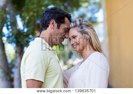 Side view of romantic couple standing by building