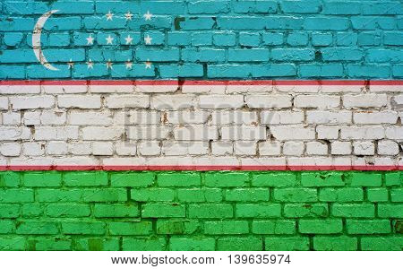 Flag of Uzbekistan painted on brick wall background texture