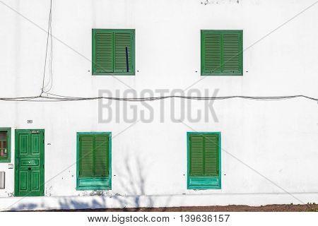 facade uf mediterranean house with closed shutterblinds at midday