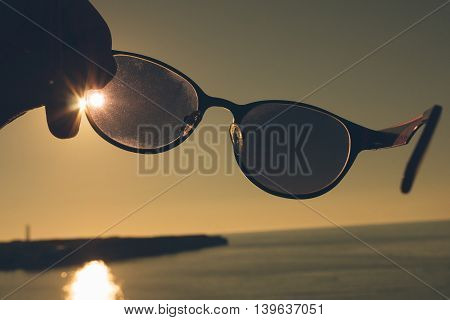 hand holding sunglasses on a background of sea sunset
