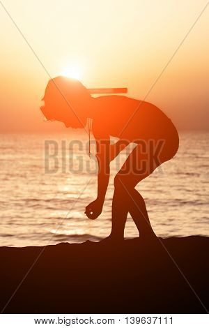 little kid with a mask and snorkel on a background of sea sunset