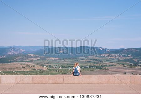 girl in denim overalls sitting on a stone fence on the background of a beautiful valley