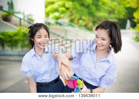 Cute Asian Thai high schoolgirls student couple in school uniform are having fun playing chasing and catching a doll with her student friend in a happy smile face expression