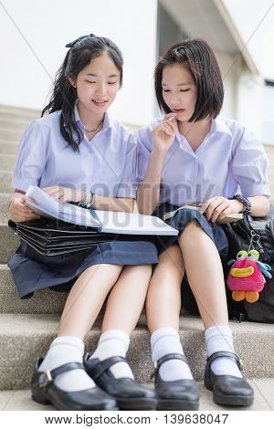 Cute Asian Thai high schoolgirls student couple in school uniform sit on the stairway discussing homework or exam with a happy smiling face together on a building stairs. Focus mainly on the book.