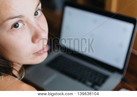 Young woman working on computer and looking at the camera