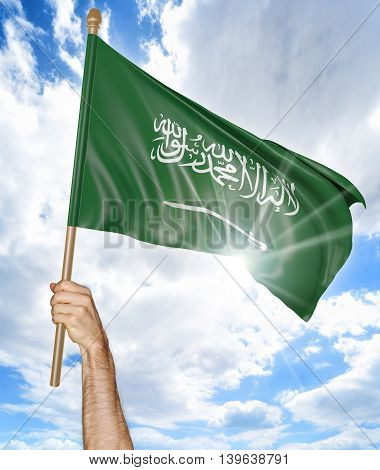 Person's hand holding the Saudi Arabian national flag and waving it in the sky, 3D rendering