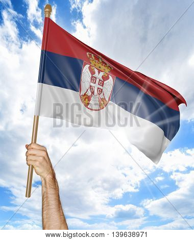 Person's hand holding the Serbian national flag and waving it in the sky, 3D rendering