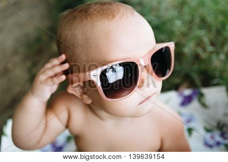Small child in large sunglasses sitting on the river Bank on a Sunny summer day