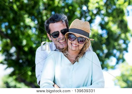 Cheerful couple embracing while standing against trees