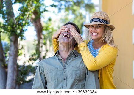 Cheerful woman covering boyfriend eyes on walkway