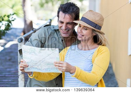 Happy couple looking in map while standing on walkway by building
