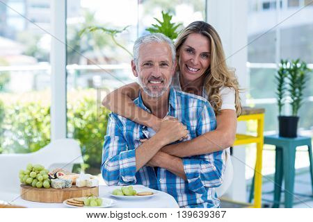 Portrait of happy woman embracing husband by table in restaurant