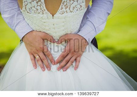 Hands of the groom hugging bride. Groom hands forming heart shape a symbol of love
