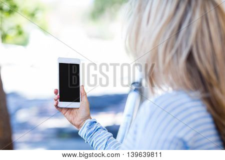 Side view of woman holding smartphone on street