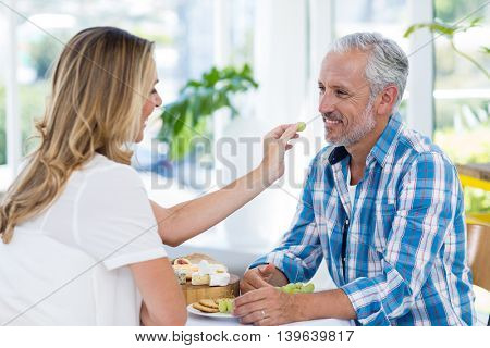 Happy woman feeding grapes to husband in restaurant