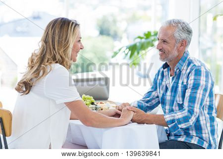 Smiling mature couple holding hands while sitting in restaurant