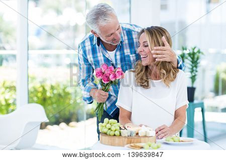 Mature man giving pink roses to happy wife by table in restaurant