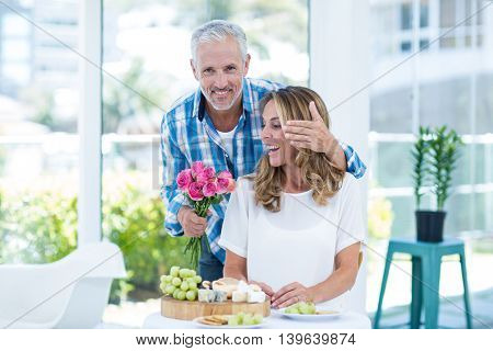 Portrait of mature man giving pink roses to happy wife by table in restaurant