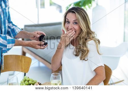 Portrait of surprised woman receiving ring by table in restaurant