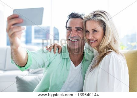 Cheerful couple taking selfie while relaxing at home