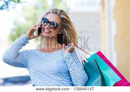 Pretty woman talking on cellphone while carrying shopping bags at street in city