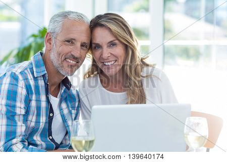Portrait of happy mature couple sitting by table in restaurant