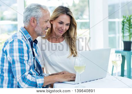 Happy couple looking in laptop on table at restaurant