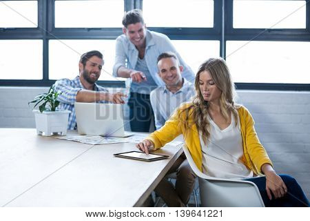 Businesswoman using digital tablet while male colleagues laughing in background at creative office