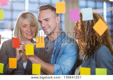 Businessman explaining to female colleagues over sticky notes in creative office