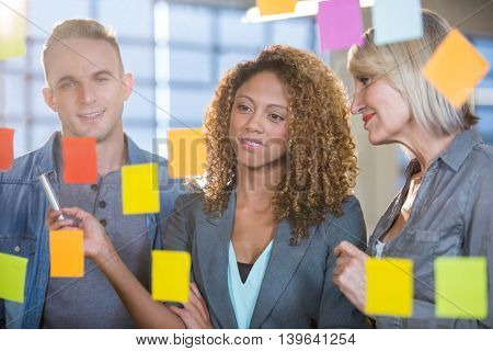 Creative business people looking at sticky notes stuck to glass during meeting
