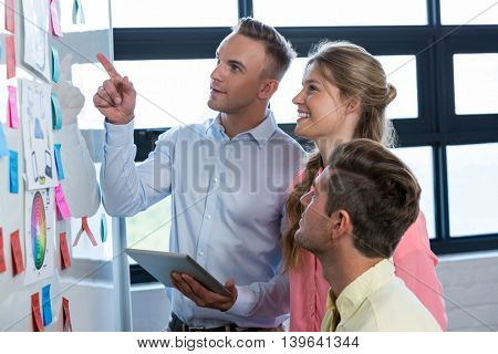 Businessman pointing at whiteboard while discussing with colleagues in office