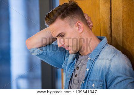 Young depressed man standing by door