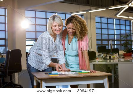 Female colleagues discussing over documents at desk in creative office