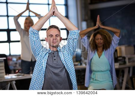 Businessman practicing yoga with coworkers in creative office