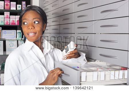 Young black pharmacist at medicine cabinet grabbing a medication